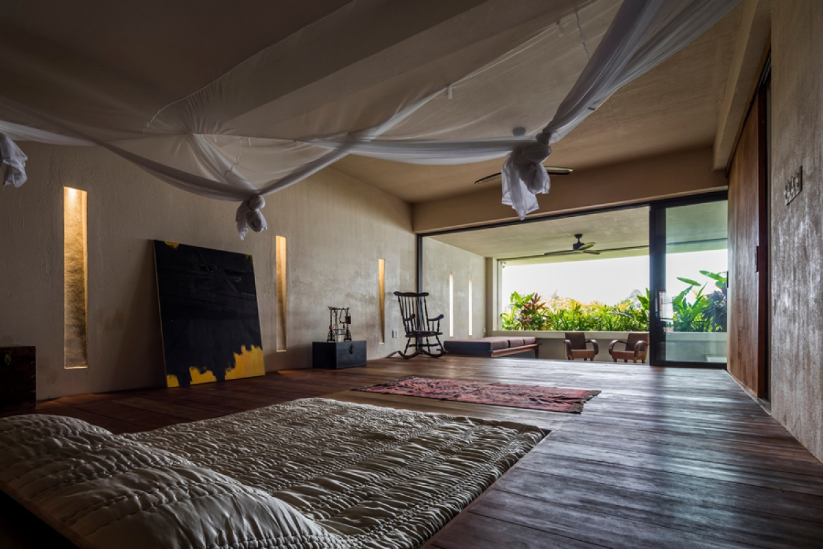 Phòng ngủ có nội thất đơn giản với tấm nệm trải trên sàn gỗ. Ô cửa lớn mở ra một ban công bên ngoài.
