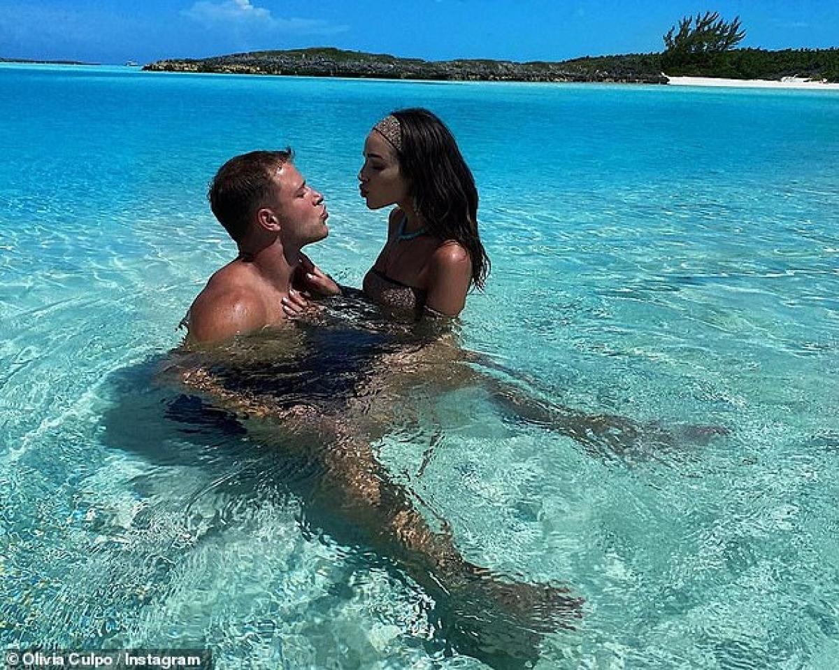 """Cô chú thích """"Ngày thi đấu đã bắt đầu. Cố lên Christian McCaffrey"""". Trong ảnh, cặp đôi quấn lấy nhau dưới làn nước biển trong xanh. Được biết, những bức ảnh này được chụp trong kỳ nghỉ từ mùa hè của cặp sao người Mỹ./."""