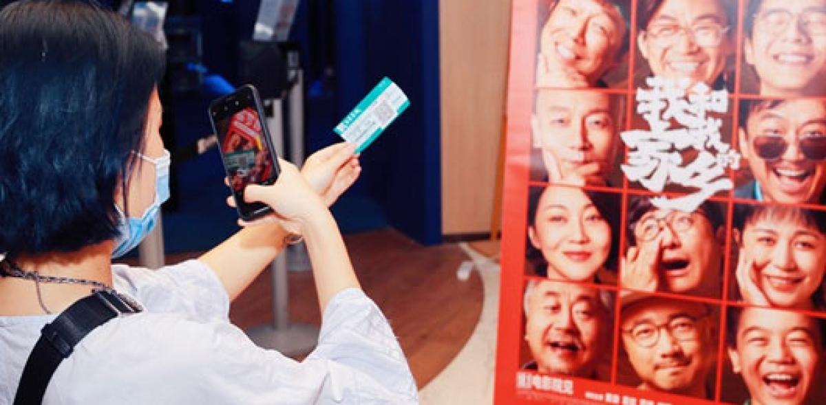 """Một khán giả chụp ảnh check- in trước poster phim """"My People, My Homeland""""."""