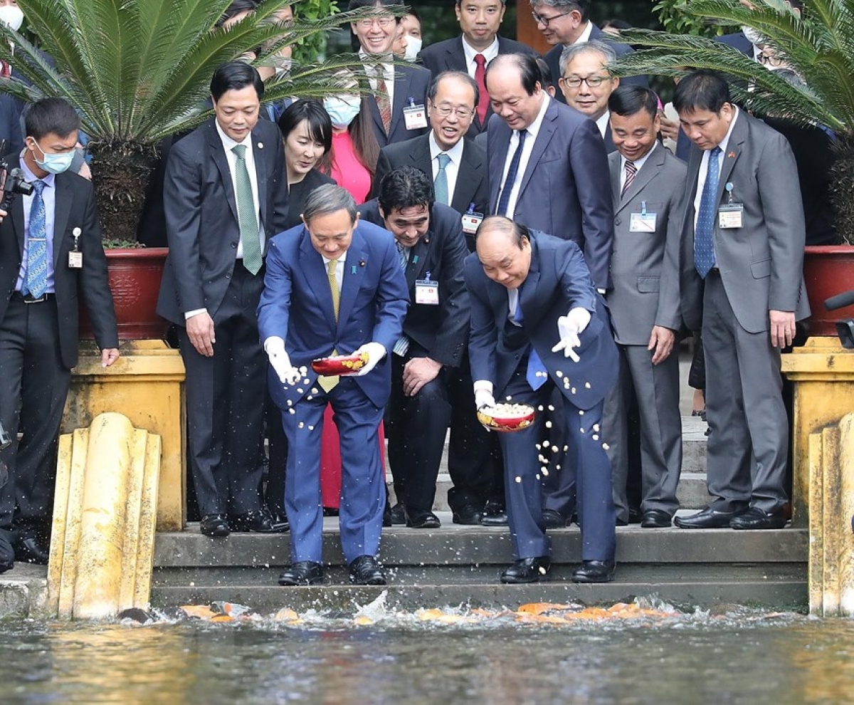 Both Government leaders take time to feed the fish in the pond located on the site.