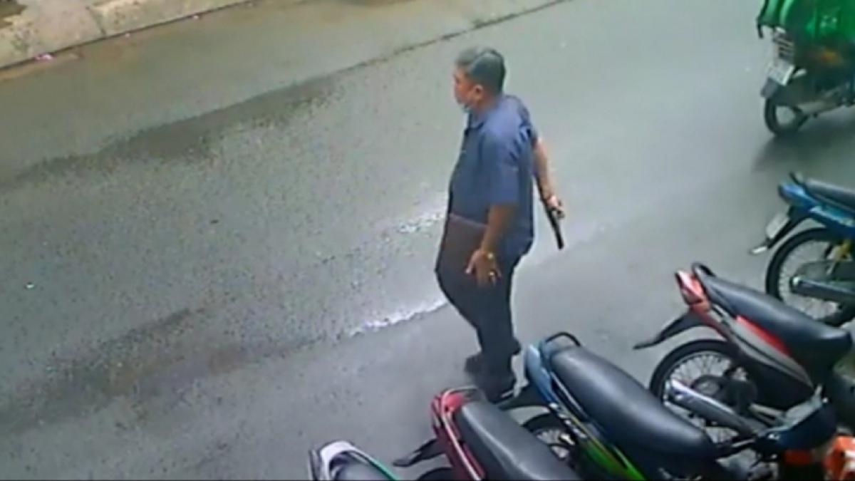 Người đàn ông cầm súng đi qua đi lại trước nhà người dân đe doạ. (ảnh cắt từ clip)