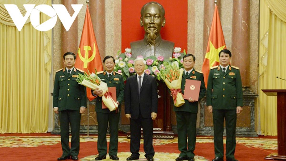 Tổng Bí thư, Chủ tịch nước Nguyễn Phú Trọng trạo Quyết định và tặng hoa cho hai tướng quân đội được thăng quân hàm.