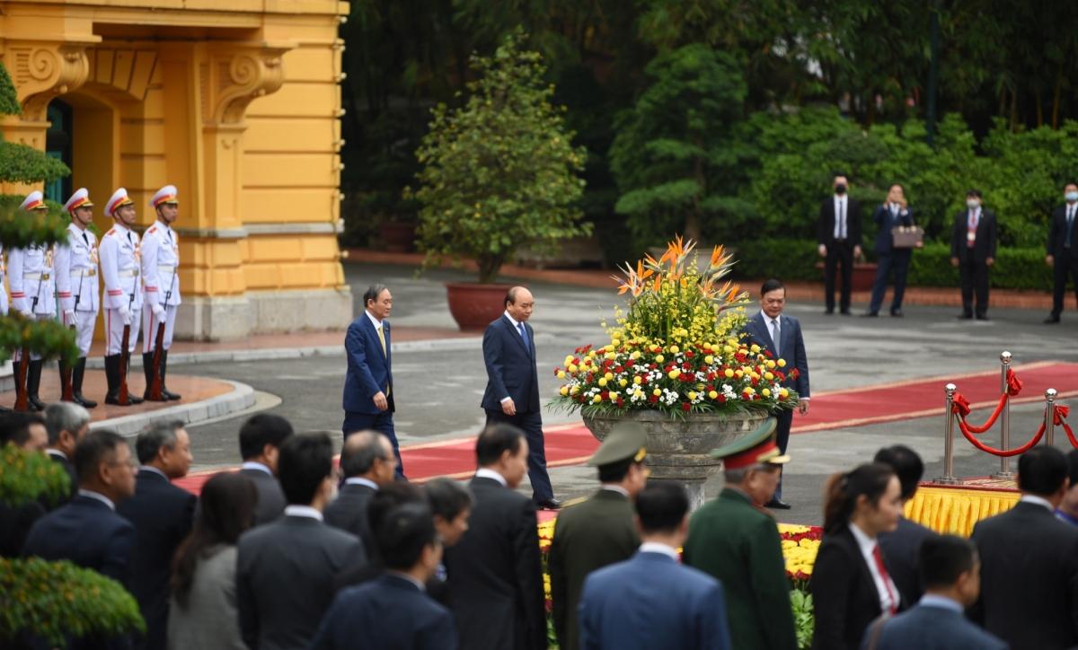 Trong tiếng nhạc chào mừng, Thủ tướng Nguyễn Xuân Phúc mời Thủ tướng Nhật Bản Suga Yoshihide bước lên bục danh dự.