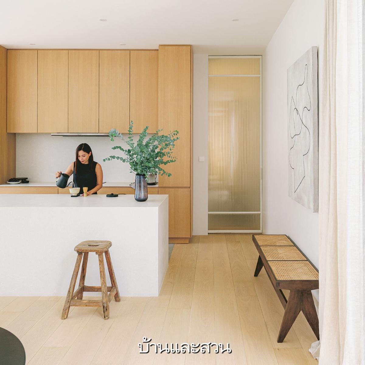 Một lọ cây xanh làm tăng sự sinh động hơn cho căn bếp tối giản chỉ với 2 màu gỗ và trắng.