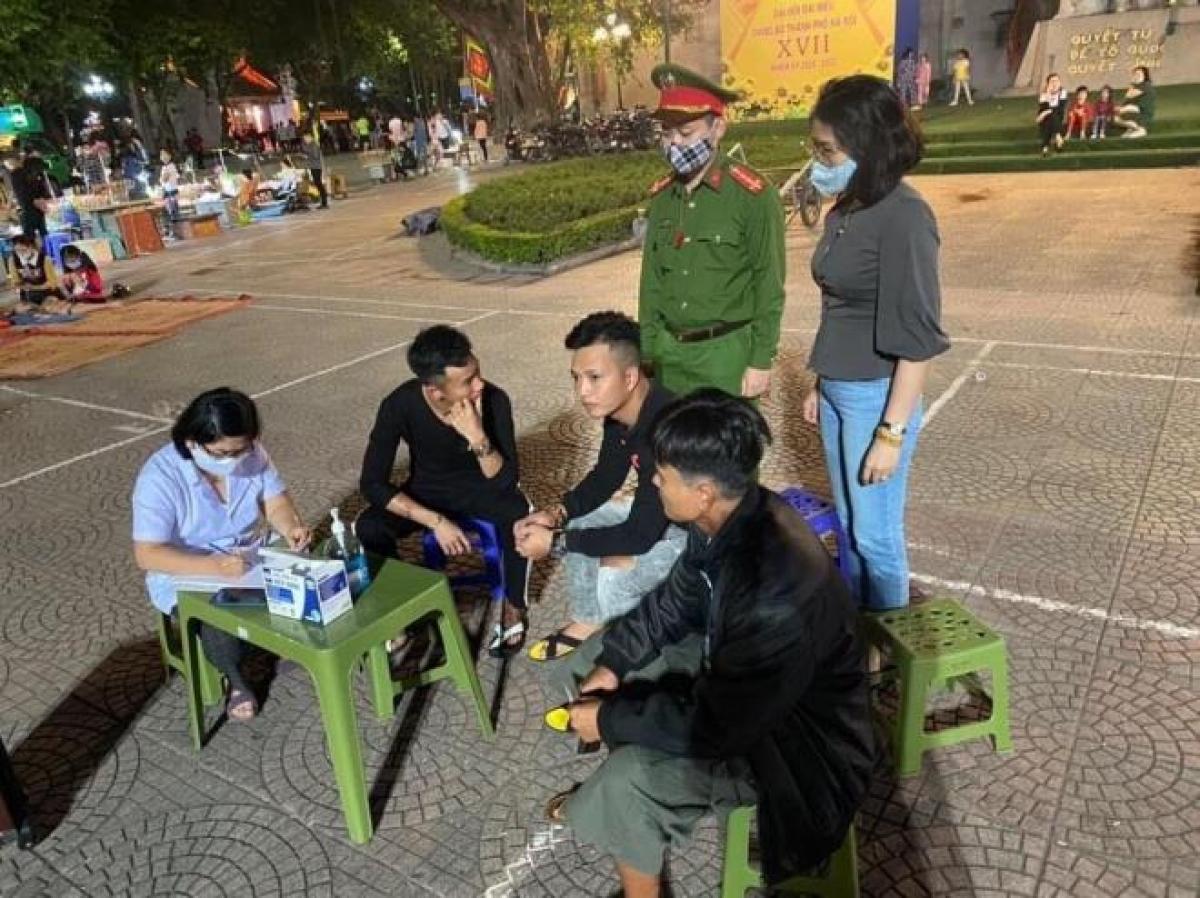 Lực lượng chức năng tuyên truyền, xử phạt những trường hợp không đeo khẩu trang tại khu vực phố đi bộ Hồ Gươm.