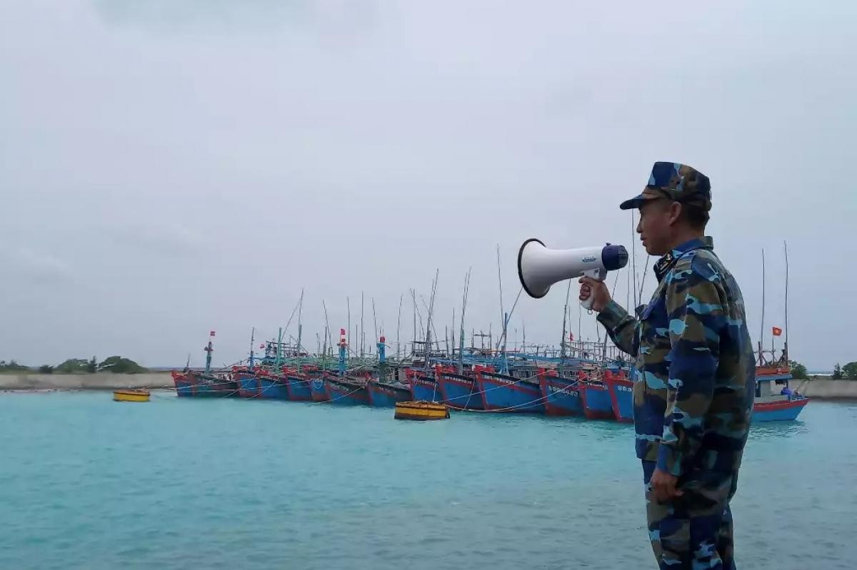 Cán bộ âu tàu Song Tử Tây hướng dẫn tàu cá vào âu tránh bão.