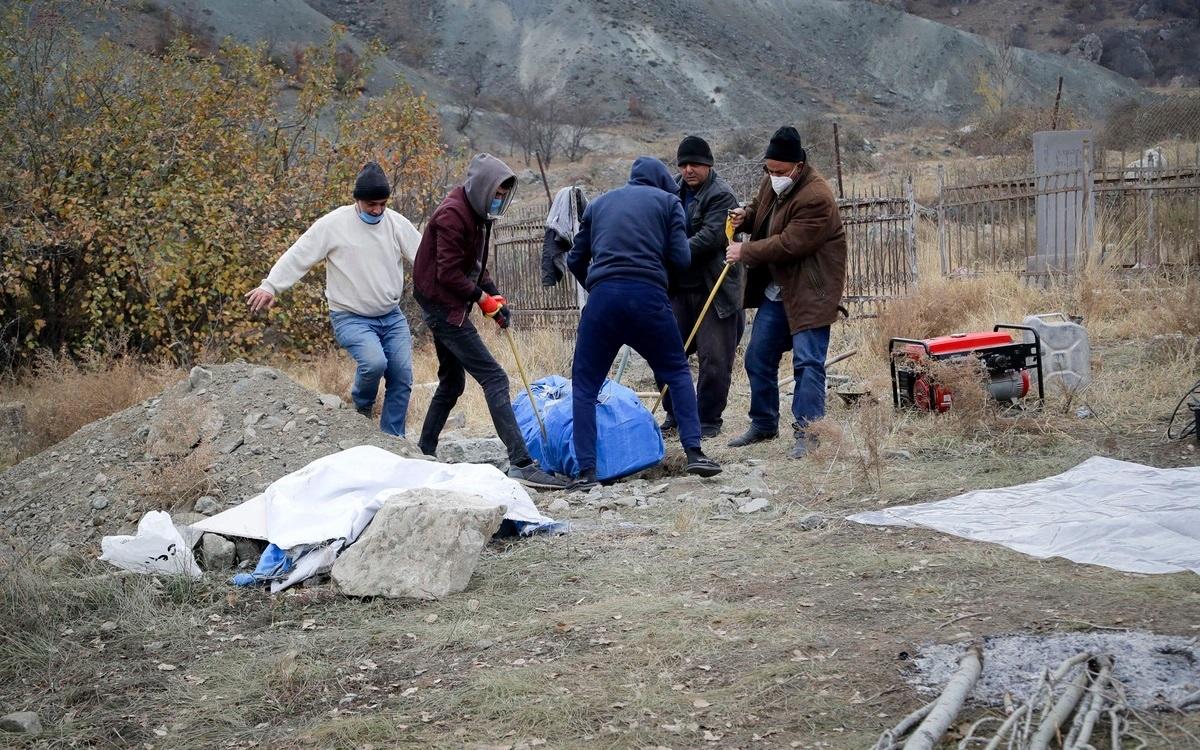Người tộc Armenia sinh sống ở vùng phải giao cho Azerbaijan đang khênh quan tài của người thân họ (vừa khai quật từ mộ) để đưa sang Armenia. Một bộ phận người Armenia ở vùng lân cận Nagorno-Karabakh đã đào hài cốt tổ tiên của mình để đưa đi trước khi các lãnh thổ họ sinh sống được chuyển giao cho Azerbaijan. Ảnh: AP.