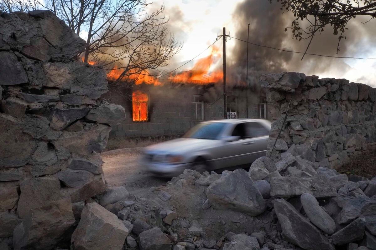 Khói lửa bốc ra từ một ngôi nhà ở khu vực do quân Armenia chiếm đóng nhưng theo kế hoạch sẽ được chuyển giao cho Azerbaijan. Ảnh: AP.