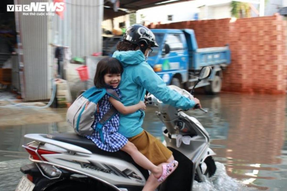 Phụ huynh vất vả chạy xe máy qua đoạn đường ngập để đưa con đi học.