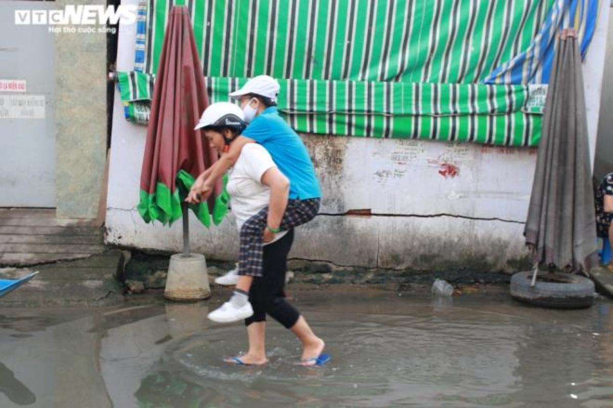 Hai người phụ nữ cõng nhau qua đoạn nước ngập.