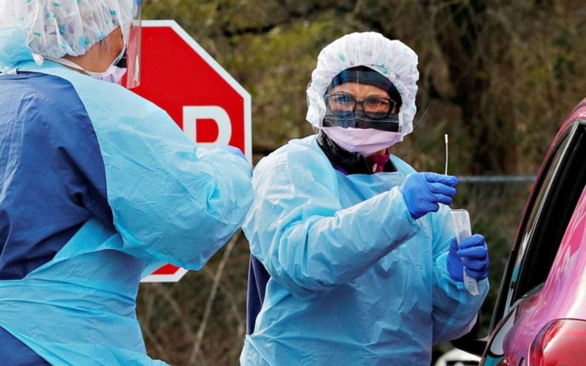 Điều dưỡng viên Mỹ lấy mẫu xét nghiệm Covid-19 tại một bãi xe. Ảnh: Reuters.