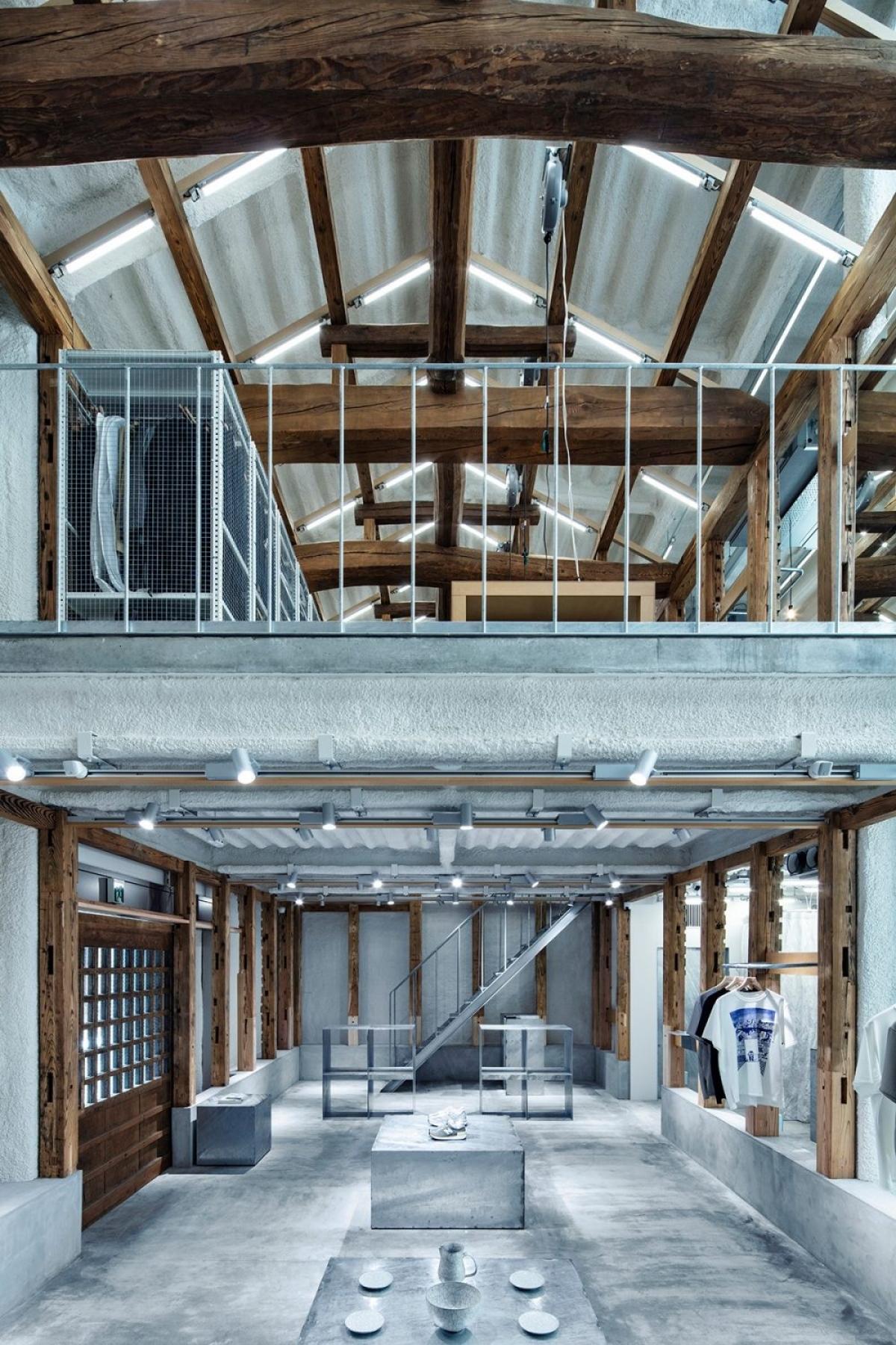 Không gian bên trong được chia làm 2 gác với khung gỗ và bê tông bao quanh. Tầng dưới là nơi để tiếp khách, ăn uống, thư giãn. Gác trên dùng để làm việc và nghỉ ngơi.