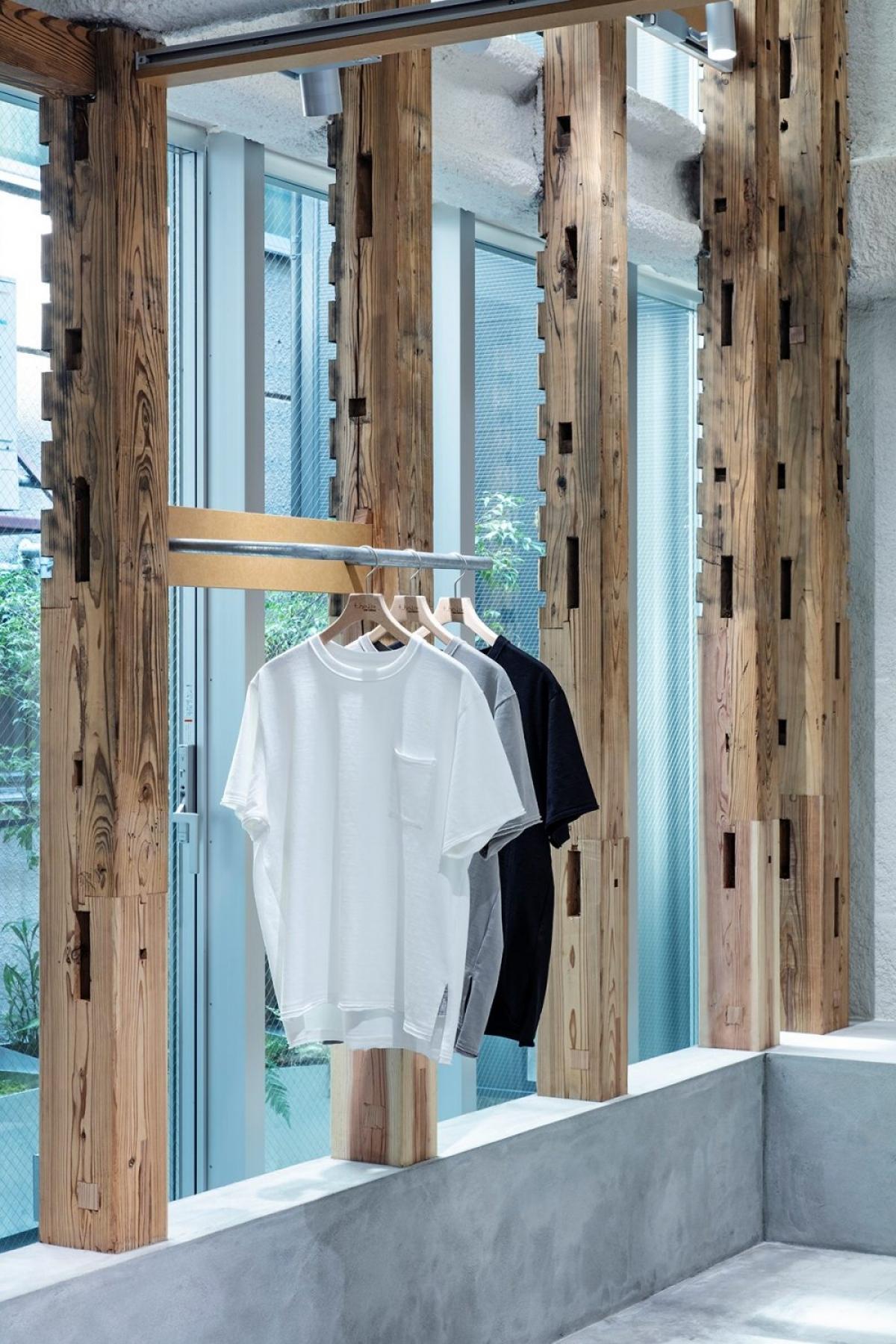 Giữa các khung gỗ có các ô lắp, gia chủ đã tận dụng một cách triệt để làm giá treo quần áo, lưu trữ giày, dép...