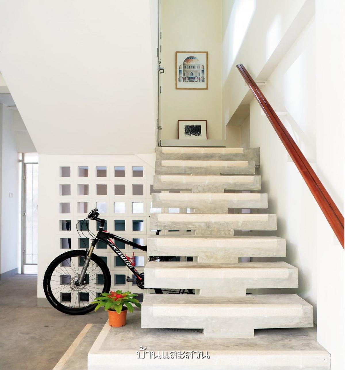 Cầu thang chính được làm bằng gạch có lỗ thông gió tốt đi kèm với chậu hoa nhỏ như bù đắp lại sự đơn điệu này.
