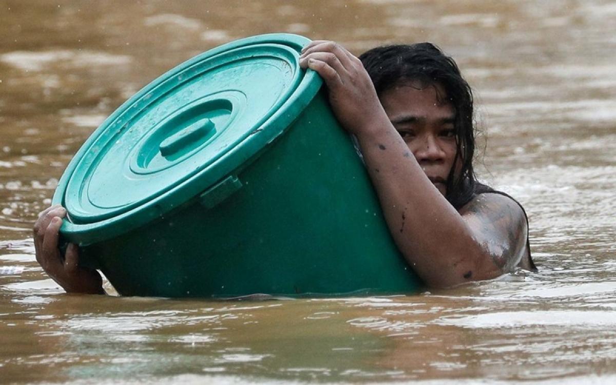 Một người dân Philippines trong lũ lụt do hậu quả của bão Vàm Cỏ. Ảnh: CNN.