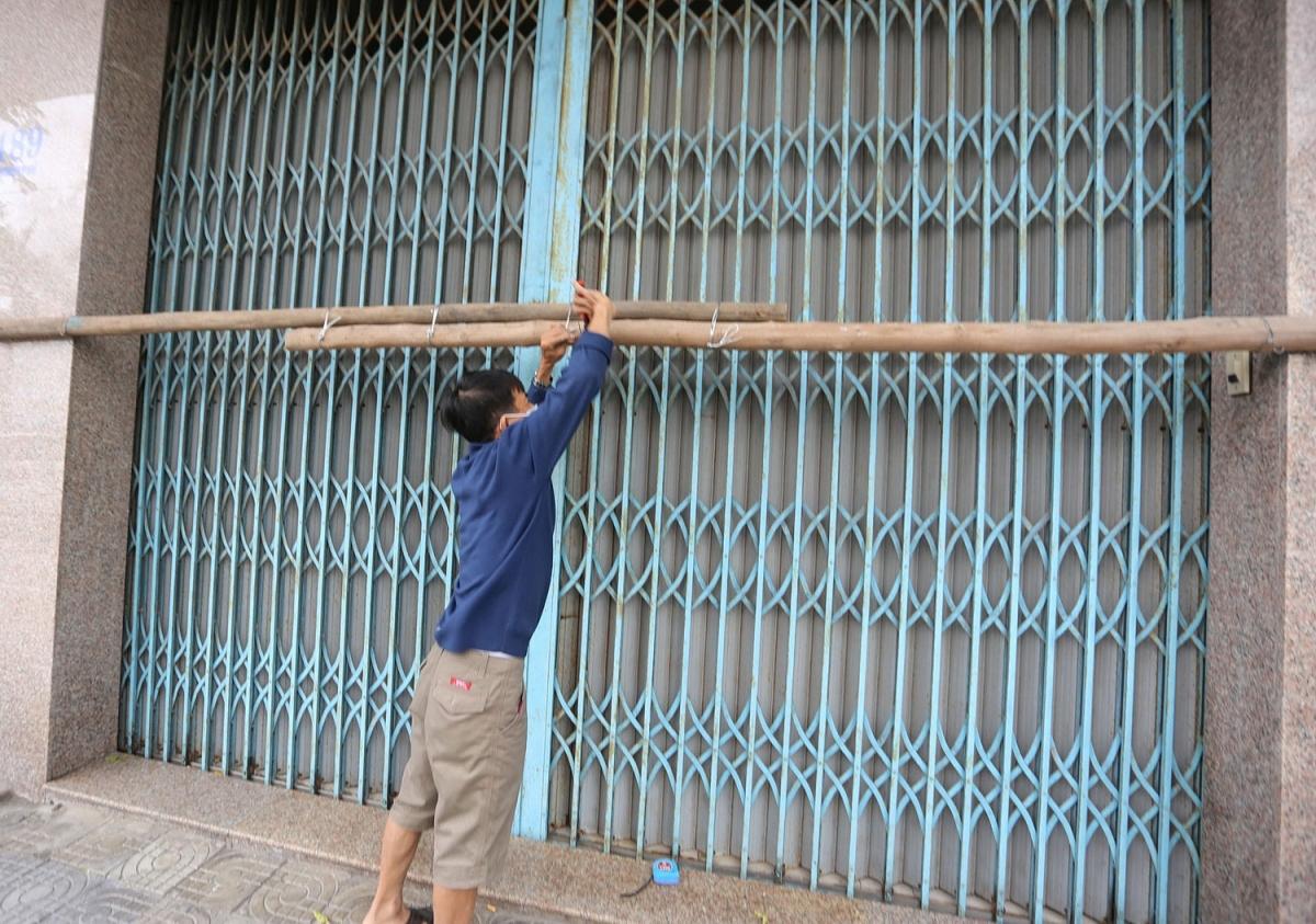 Người dân ở đường biển Nguyễn Tất Thành chằng néo cửa trước để tránh gió giật bung cửa.