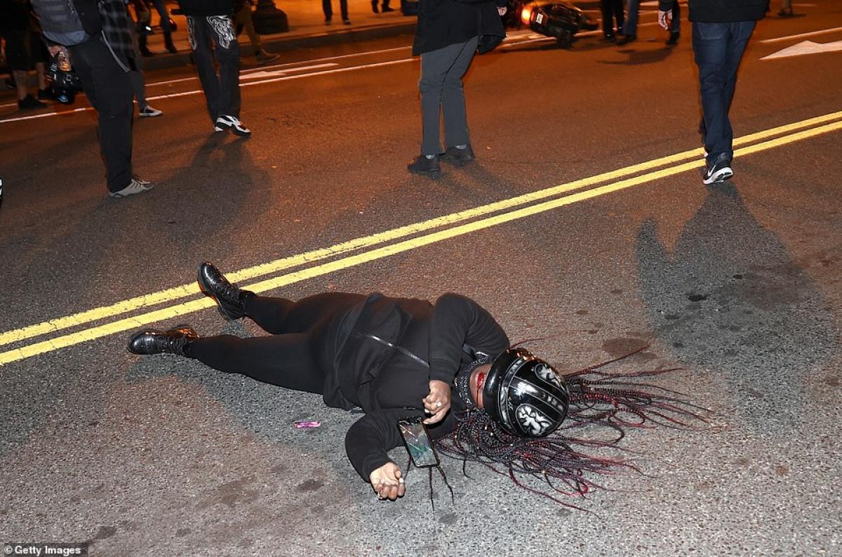 Một phụ nữ thuộc phe ủng hộ Biden bị thương nằm bên vệ đường ở thủ đô Washington (Mỹ).