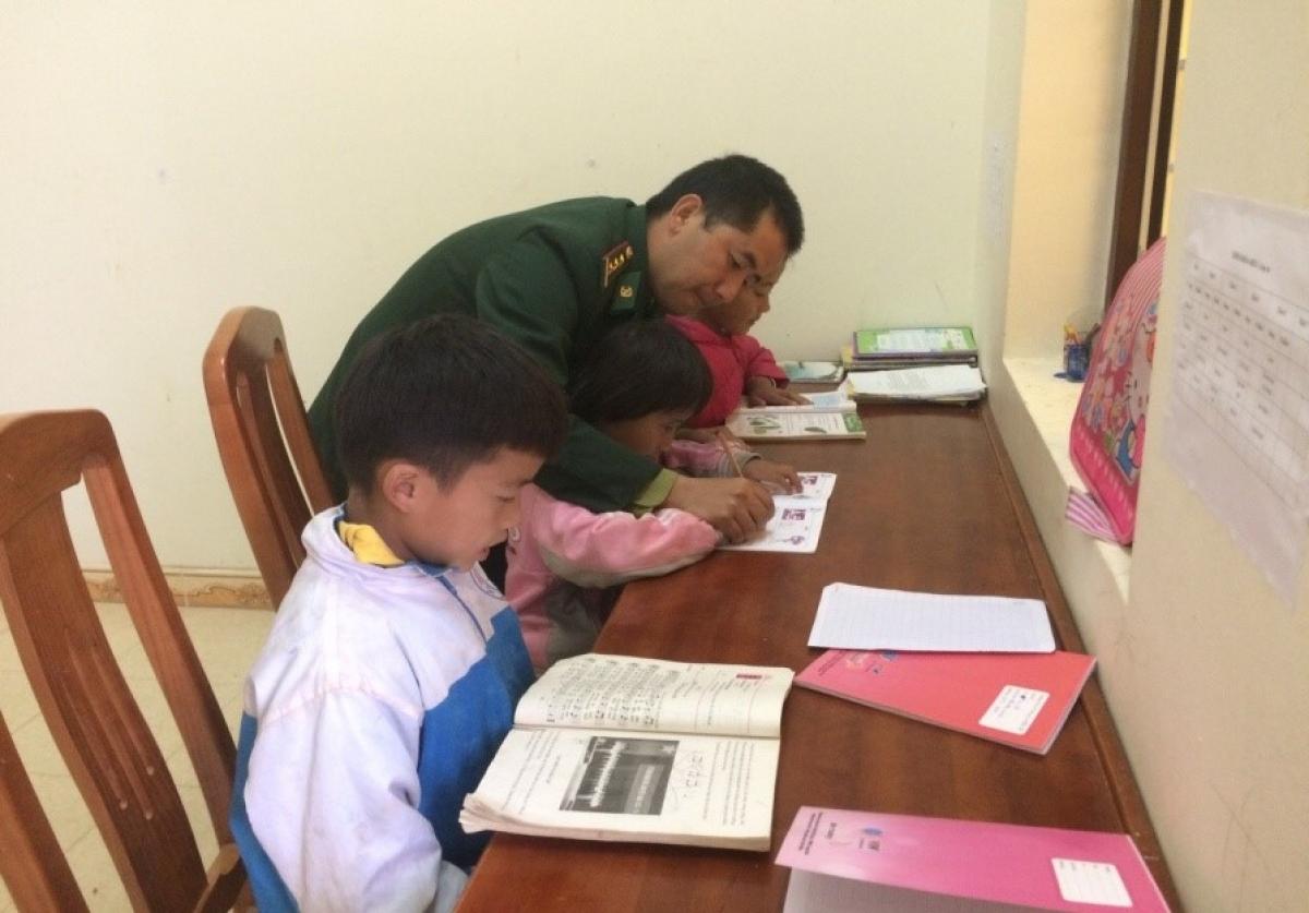 Đại úy Vừ Mí Chứ hướng dẫn các con học bài. (Ảnh: NVCC)