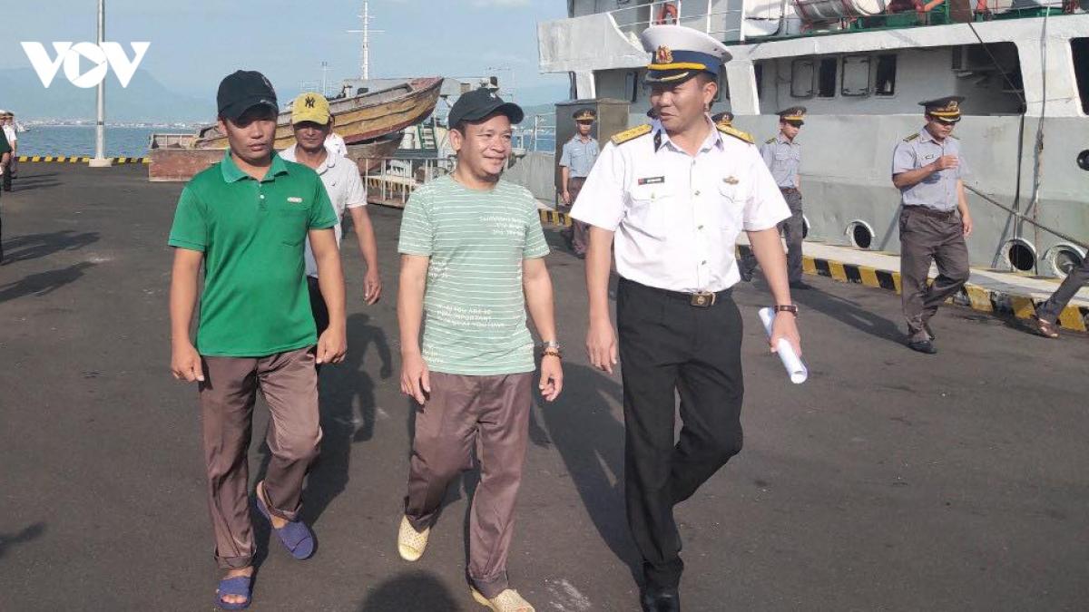 Thượng tá Trần Mạnh Chiến, Chủ nhiệm Chính trị Vùng 4 Hải quân (áo trắng bên phải) đón ngư dân gặp nạn về cảng.