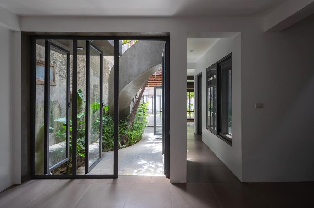 Sàn bê tông, tường kính, đồ nội thất gỗ phối hợp thật nhịp nhàng.