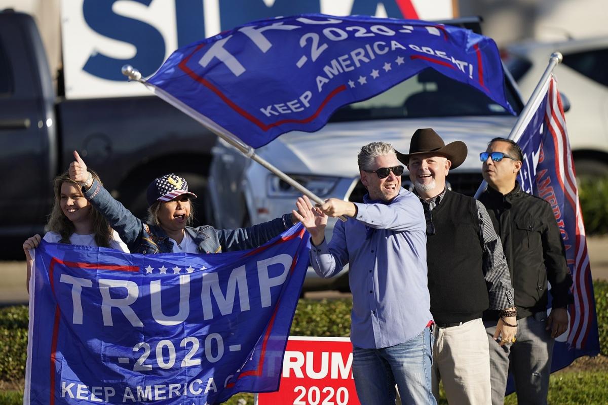 Những người ủng hộ Tổng thống Trump cổ vũ cho ứng viên của mình gần một điểm bỏ phiếu ở Houston ngày 3/11. Ảnh: AP.
