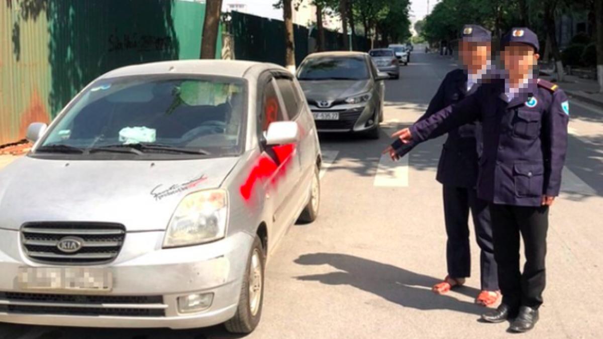 Nhóm bảo vệ xịt sơn đỏ lên xe ô tô.