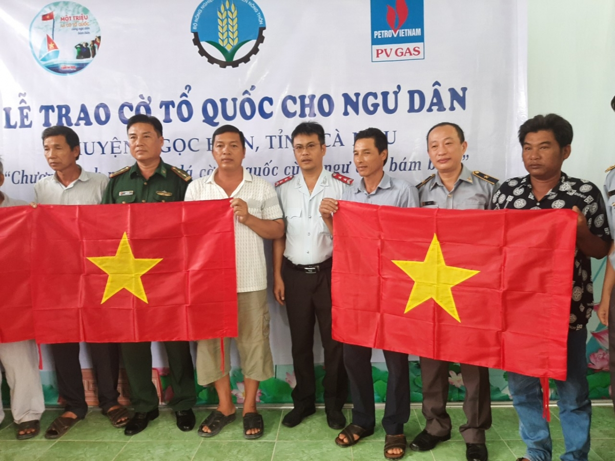 Ông Hà Lê (thứ 2 từ phải sang) Phó Cục trưởng Cục Kiểm ngư cùng lãnh đạo địa phương trao cờ cho ngư dân Ngọc Hiển. (Ảnh: Đình Trọng - Cục Kiểm ngư)