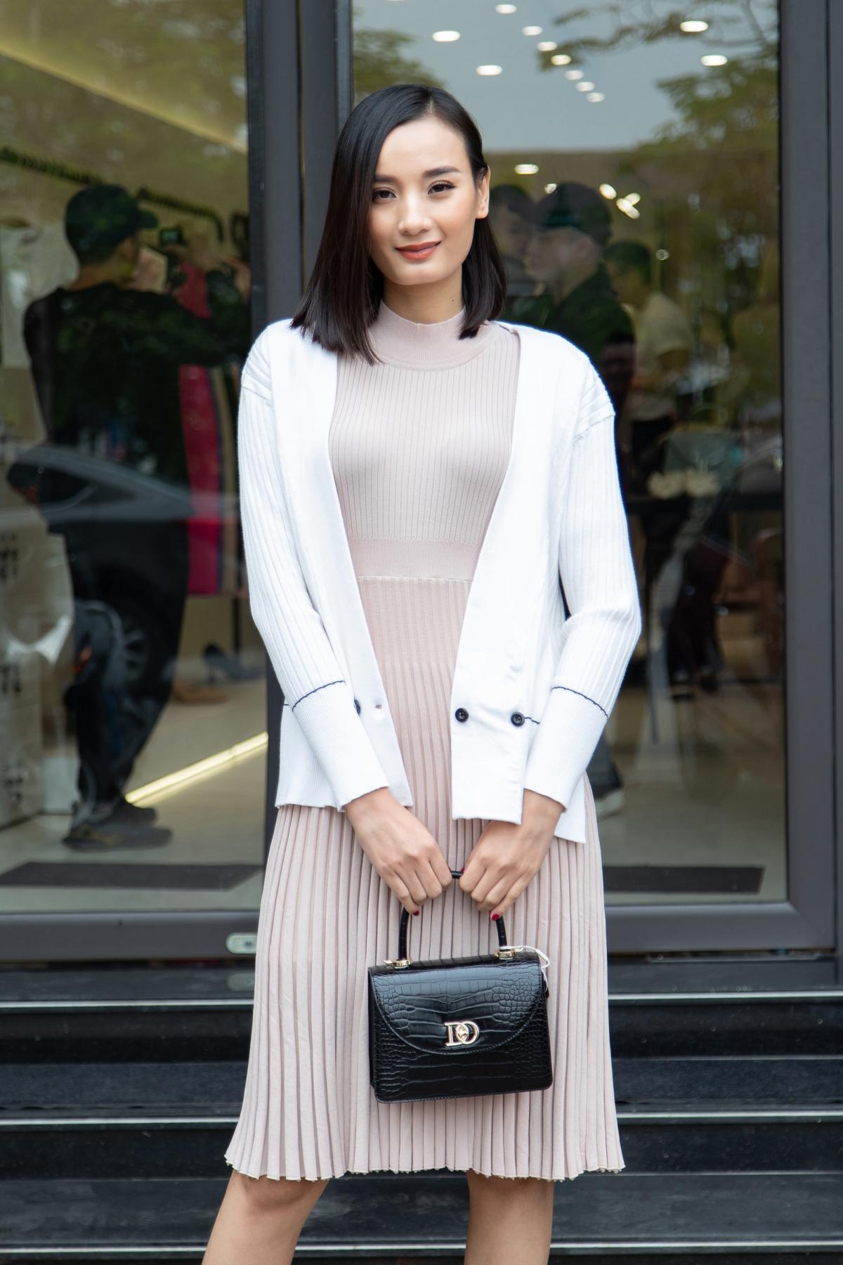 Nàng thơ Lê Thuý diện váy dệt kim màu be cổ điển phối áo khoác sắc trắng trẻ trung bên ngoài.