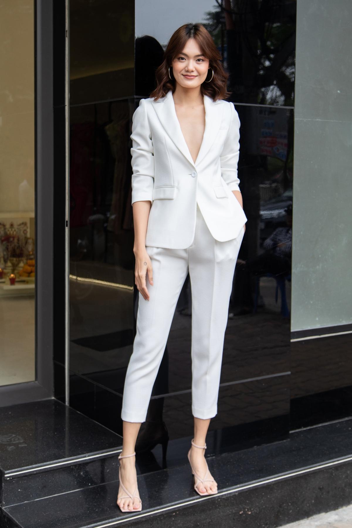 Cũng với sắc trắng, người mẫu Lê Thanh Thảo lại chọn kiểu vest phom rộng với đường xẻ ngực sâu, trông vừa thanh lịch nhưng cũng không kém phần gợi cảm. Cô phối cùng chiếc túi màu nâu nhạt, phù hợp với mùa thời trang cuối năm.