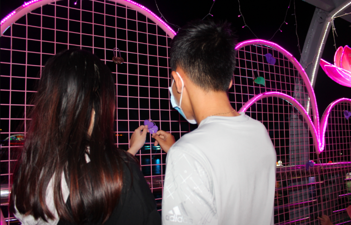 Các bạn trẻ háo hức với trái tim hồng gắn khóa tình yêu trên cầu đi bộ Ninh Kiều
