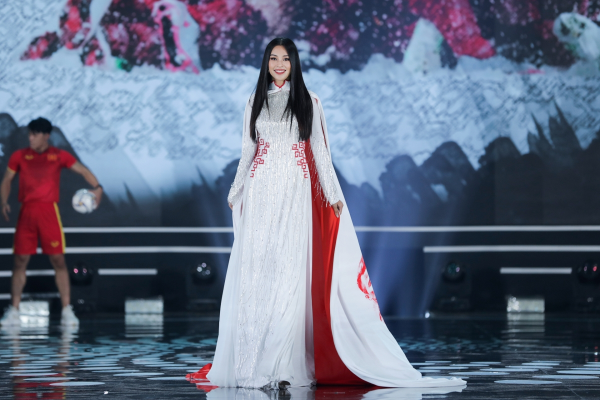 Hoa hậu Tiểu Vy bước đi tự tin mang khí thế khác hẳn áo dài có hình vẽ tranh cổ động cho đội tuyển U23 VN do Ngô Nhật Huy thiết kế.