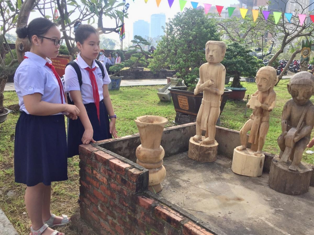 Nhiều học sinh xem tượng điêu khắc gỗ của người Cơ Tu.