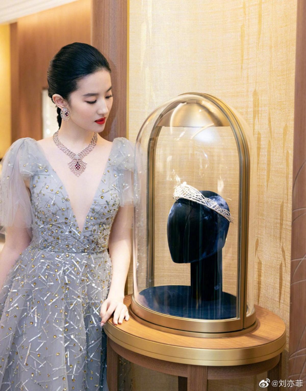 Làn da trắngmịn nổi bật trong thiết kế đầm xanhbồng bềnh, lấp lánh.