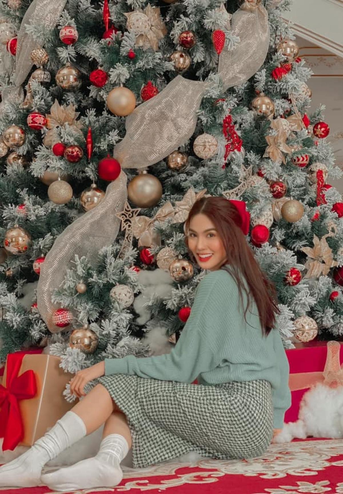 Lan Khuê được khen ngày càng xinh đẹp và nhuận sắc sau khi sinh con gái. Người đẹp diện chân váy kẻ đơn giản, áo len màu xanh bạc hà, đánh son đỏ bên cây thông Noel trang trí cầy kỳ tại nhà.