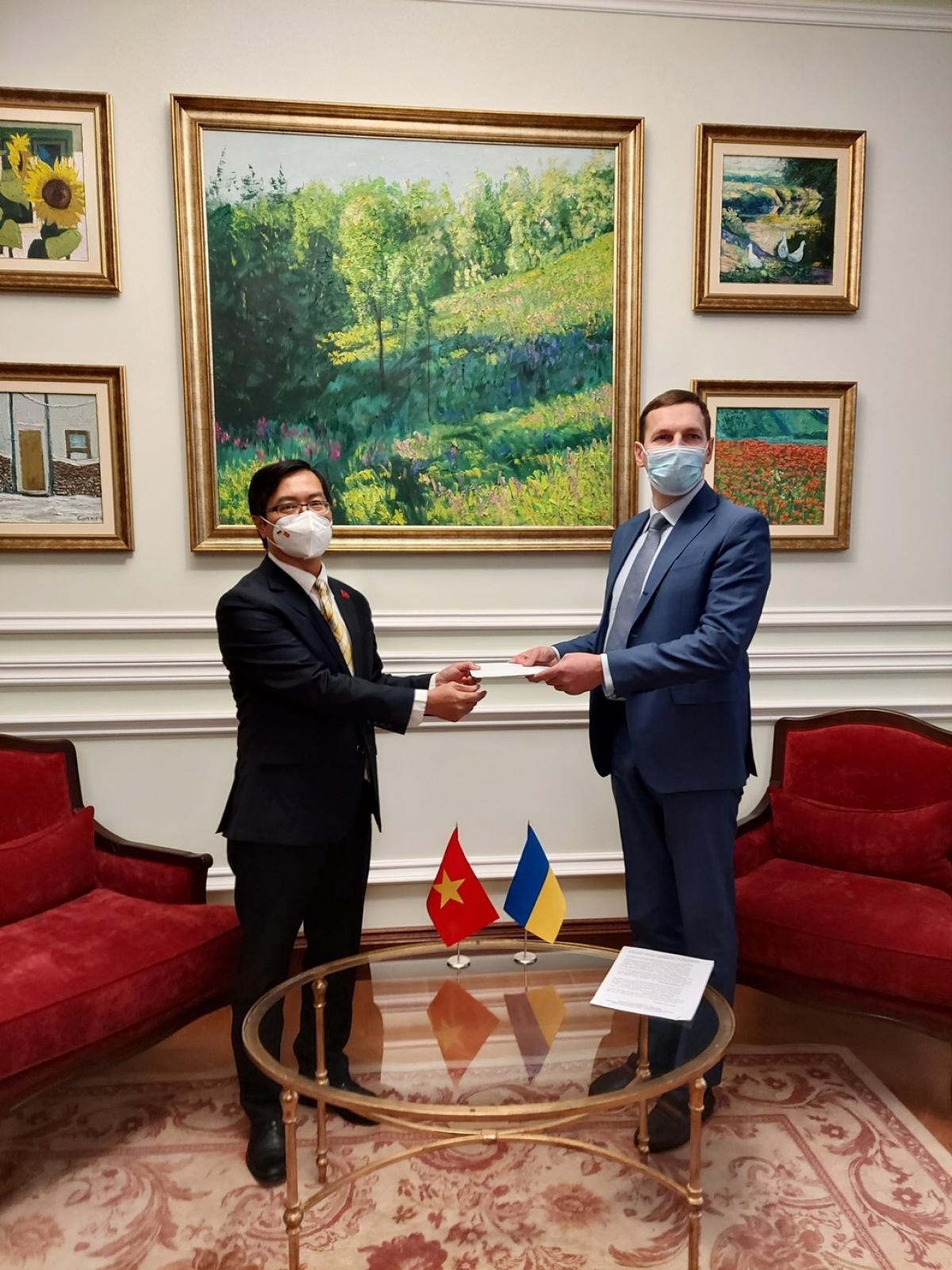 Đại sứ Nguyễn Hồng Thạch(trái) trình bản sao Ủy nhiệm thư cho Thứ trưởng Bộ Ngoại giao UkrainaYevheniy Yenin.