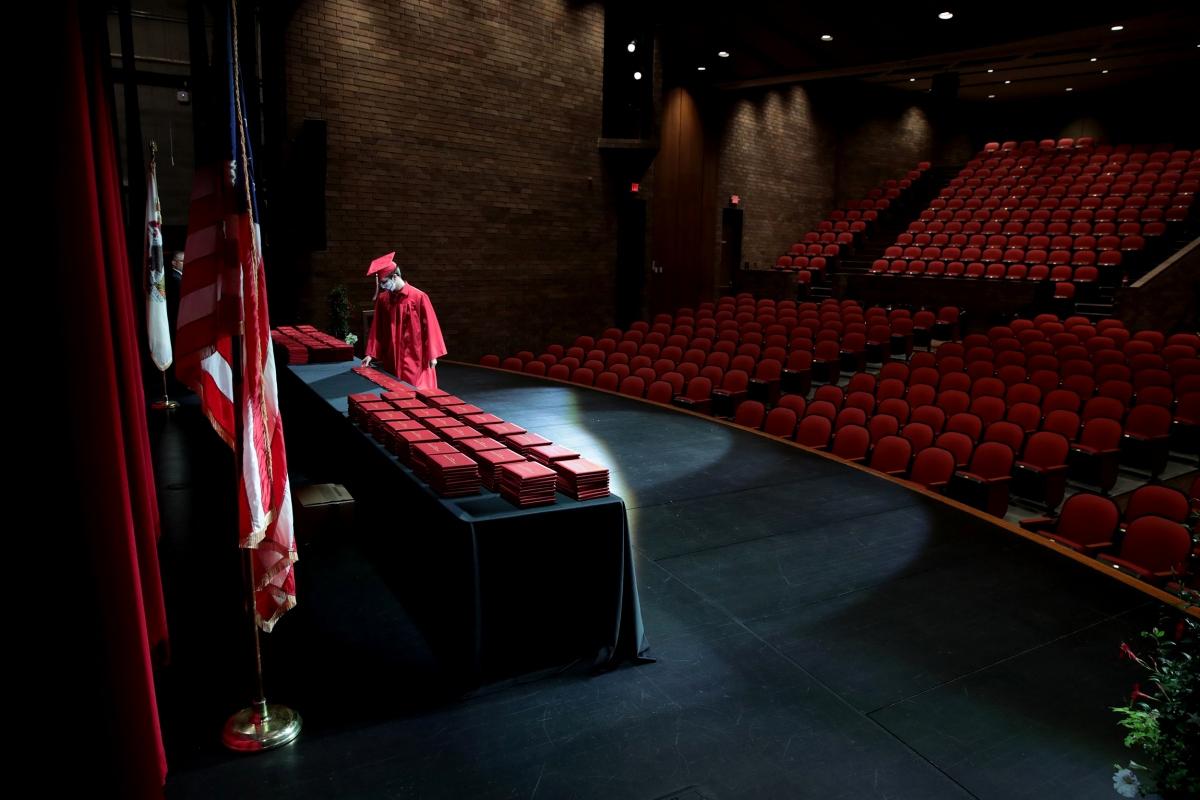 Một học sinh nhận bằng tốt nghiệp tại Trường Trung học Cộng đồng Bradley-Bourbonnais trong một khán phòng trống rỗng, không có bạn bè, gia đình hoặc người thân nào được tham dự do đại dịch Covid-19. Ảnh: Getty Images