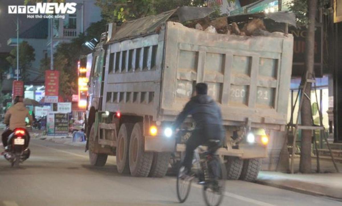 """Một chiếc xe tải cơi nới thành thùng, chở đá che chắn thùng sơ sài dừng đỗ bên đường ở thị trấn Núi Đèo, chờ đến giờ """"xuất kích"""". Những hòn đá trên thùng xe nhô ra như sắp rơi xuống đầu người đi đường."""