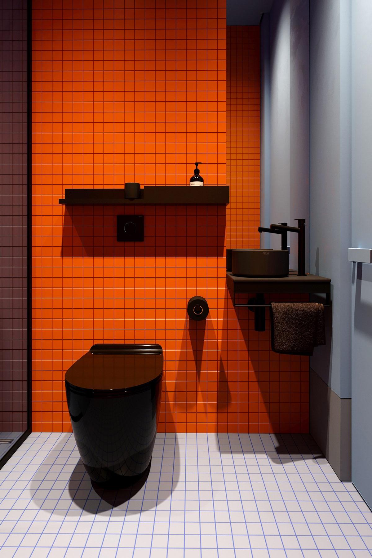 Đối lấp hoàn toàn với phòng ngủ, không gian tắm vô cùng rực rỡ với màu cam và một chút dịu nhẹ của sọc xanh của sàn.