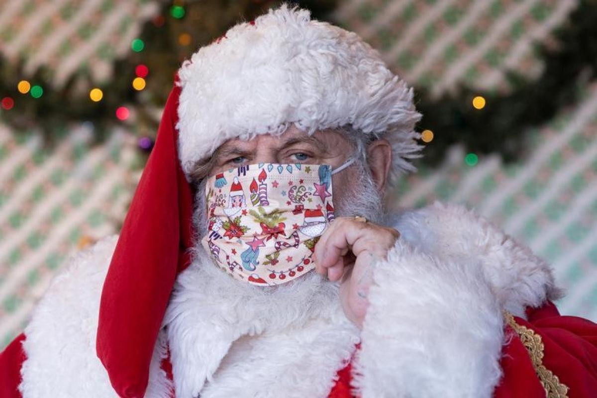 Dana Friedman đã hóa trang thành ông già Noel vào mỗi mùa Giáng sinh kể từ năm 2001. Ông đang chỉnh lại khẩu trang trước khi chào một đứa trẻ tại Trung tâm mua sắm Bay Terrace, quận Queens, thành phố New York, Mỹ. Ảnh: Reuters