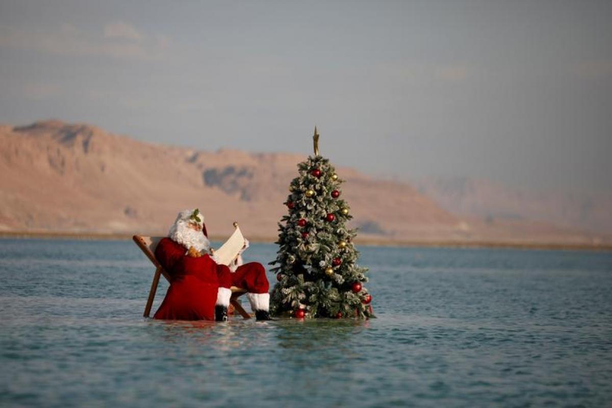 Issa Kassissieh mặc trang phục ông già Noel và tạo dáng chụp ảnh bên cạnh cây thông trên một hồ muối ở Biển Chết.Đây là một phần trong chiến dịch của Bộ Du lịch Israel nhằm mang đến không khí Giáng sinh sớm giữa bối cảnh đại dịch Covid-19 vẫn tiếp diễn. Ảnh: Reuters