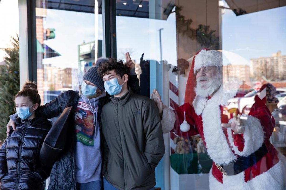 Dana Friedman chụp ảnh cùng một gia đình qua cửa kính. Ảnh: Reuters