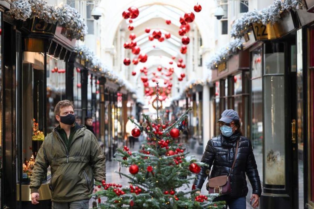 Người dân đi bộ qua trung tâm thương mại Burlington Arcadetại London (Anh) được trang trí với những cây thông Noel. Ảnh: Reuters