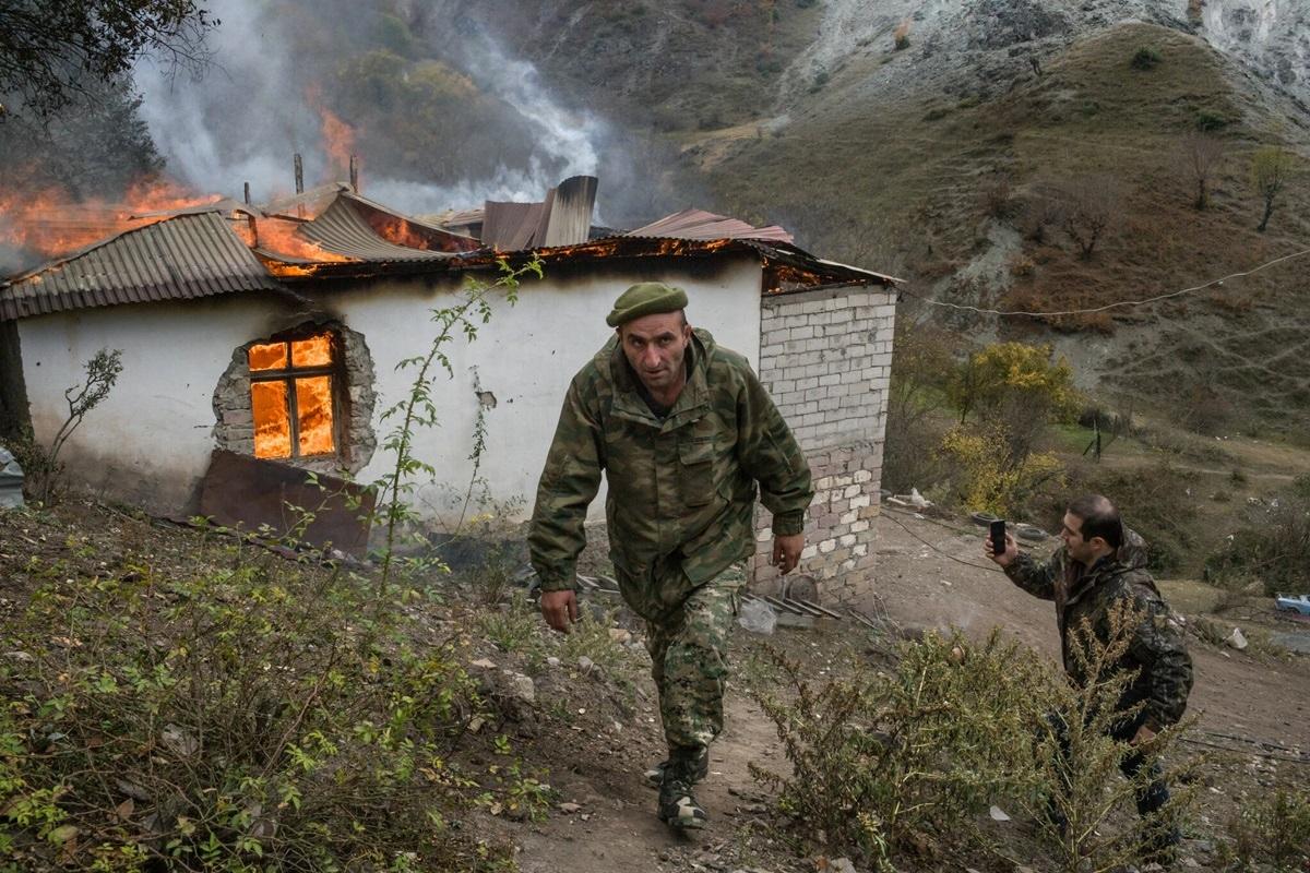 Binh sĩ người Armenia bước qua một ngôi nhà đang cháy gần tu viện Dadivank ở Kelbajar.
