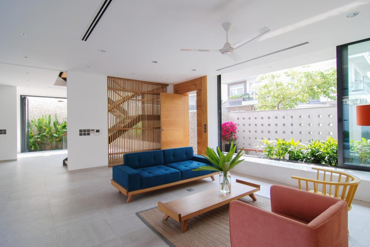 Phòng khách được đặt bên một ô cửa sổ lớn, tràn ngập ánh sáng tự nhiên. Các không gian được tổ chức kết nối, liên thông để tạo sự thoáng mở.