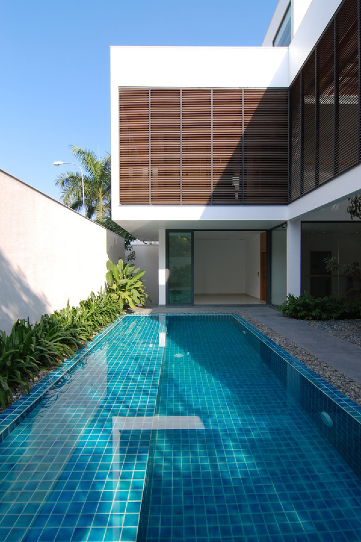 Không gian phòng khách mở ra bể bơi xanh mát phía sau nhà. Tầng trên sử dụng hệ lam chắn nắng tạo sự kín đáo mà vẫn thông thoáng.