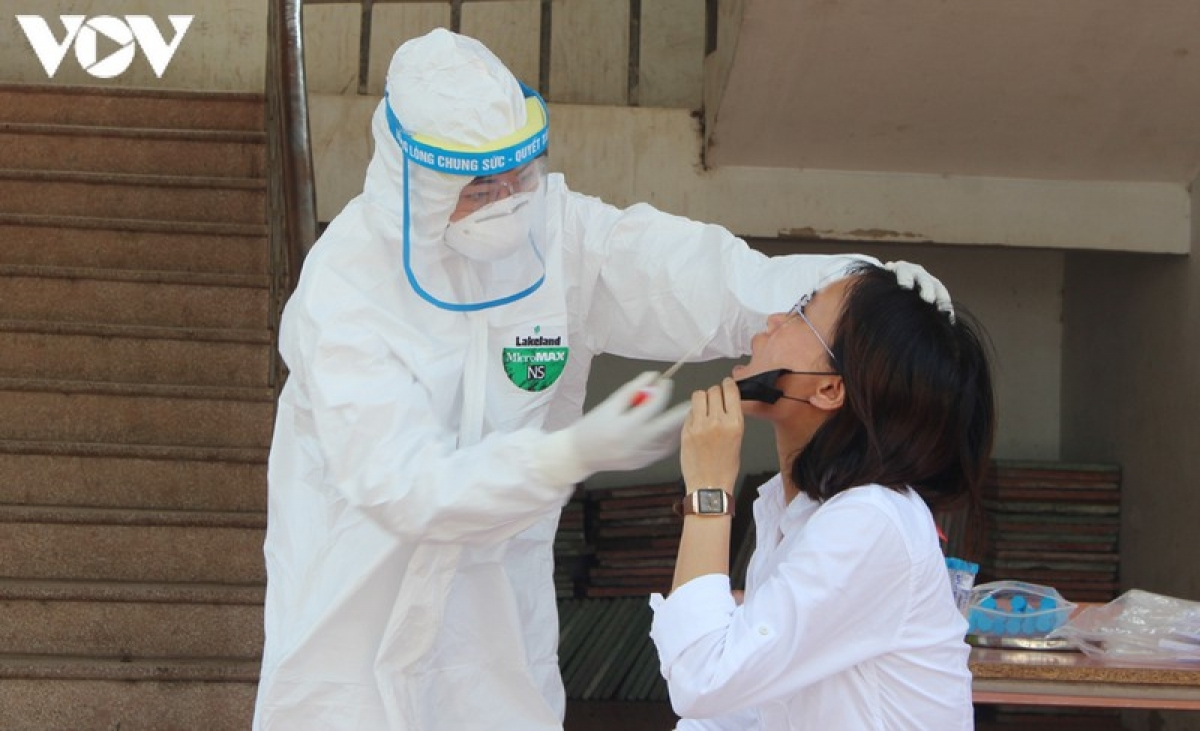 A medical worker in protective suit is taking a girl's sample for COVID-19 testing.