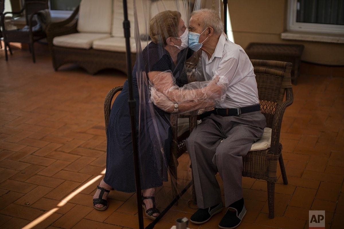 Agustina Canamero, 81 tuổi và Pascual Perez, 84 tuổi, trao nhau nụ hôn qua tấm chắn nhựa tại một viện dưỡng lão ở Barcelona (Tây Ban Nha) để phòng dịch Covid-19. Ảnh: AP