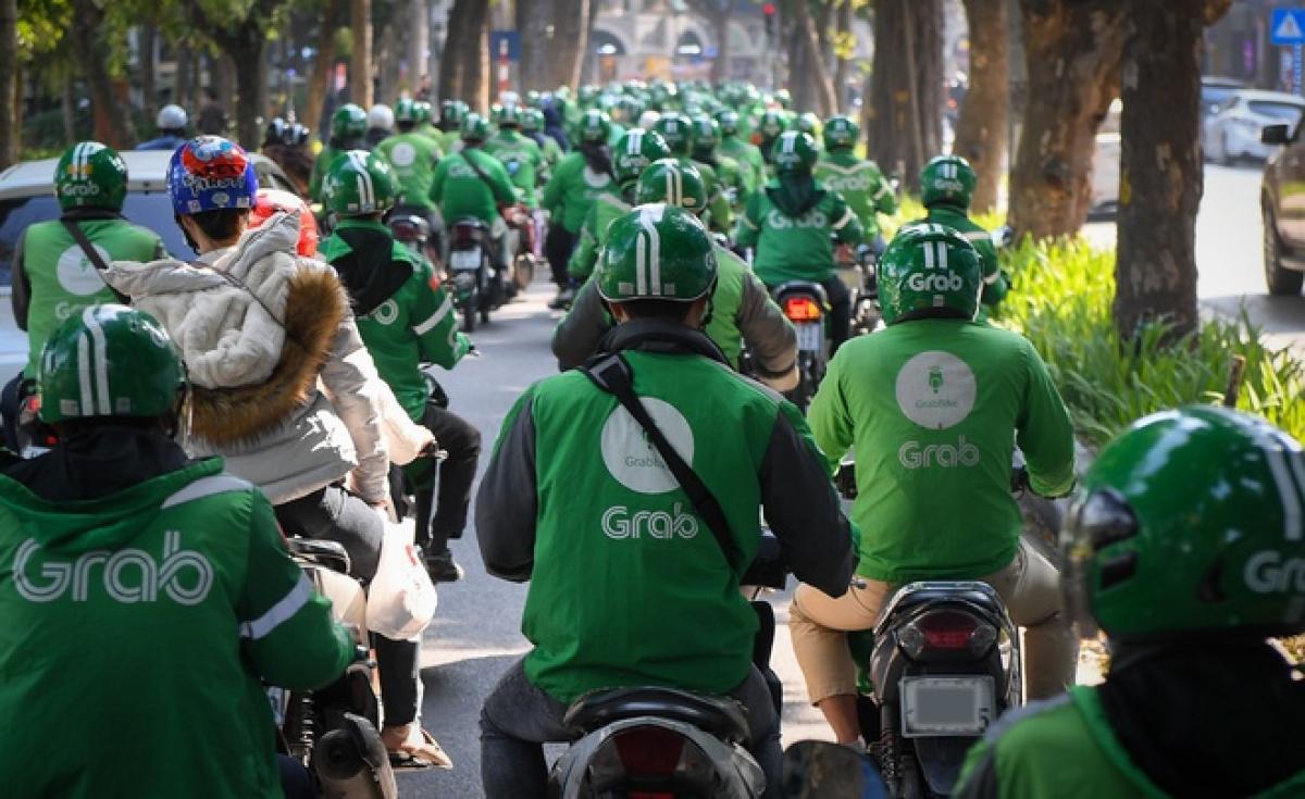 Việc Grab tăng giá cước xe và tăng khấu trừ thuế đã khiến hàng trăm tài xế GrabBike biểu tình phản đối. (Ảnh minh họa: KT)