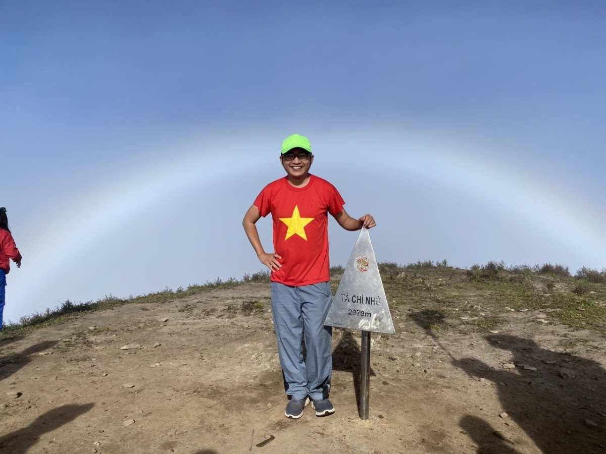 A tourist snaps an image upon successfully conquering the peak of Ta Chi Nhu Mountain.
