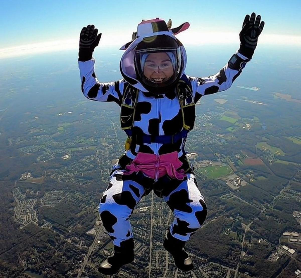 Nụ cười rạng rỡ của người phụ nữ khi bay dù lượn trên bầu trời.